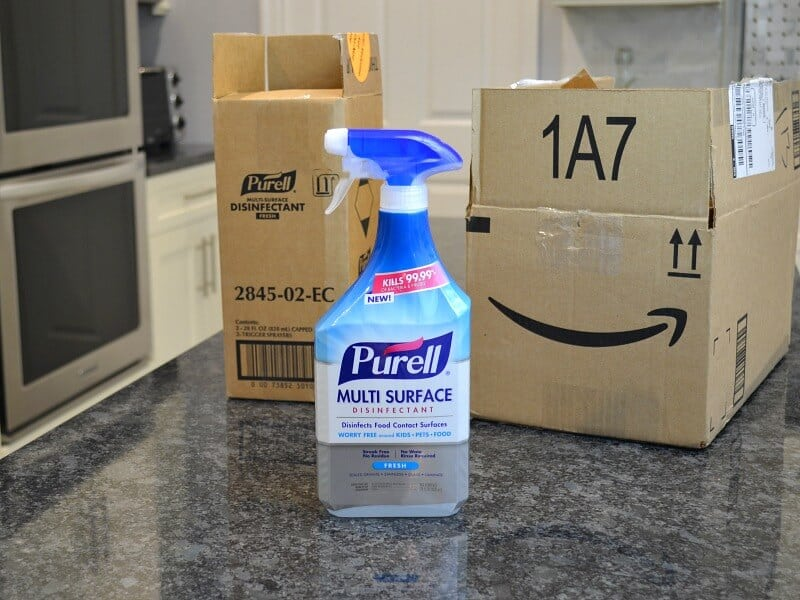 bottle of granite cleaner on black counter top with 2 shipping boxes in background