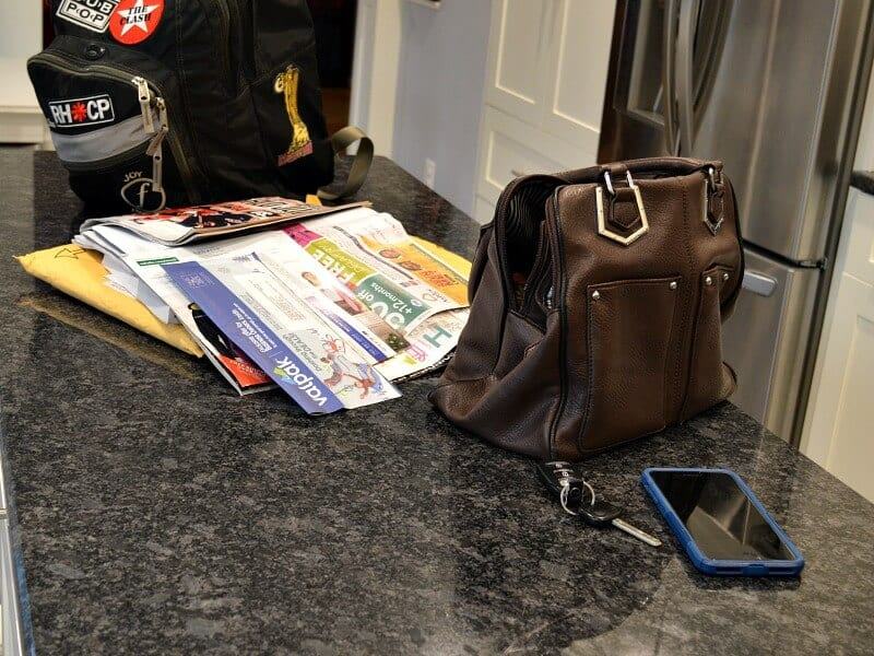 purse, phone, keys, stack of mail and backpack on kitchen counter