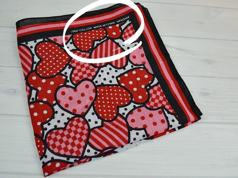 bandanna with hearts and circle around the text on edge of fabric