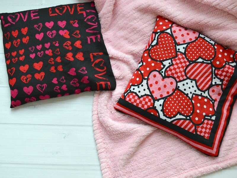 2 rice heat packs with hearts on pink blanket