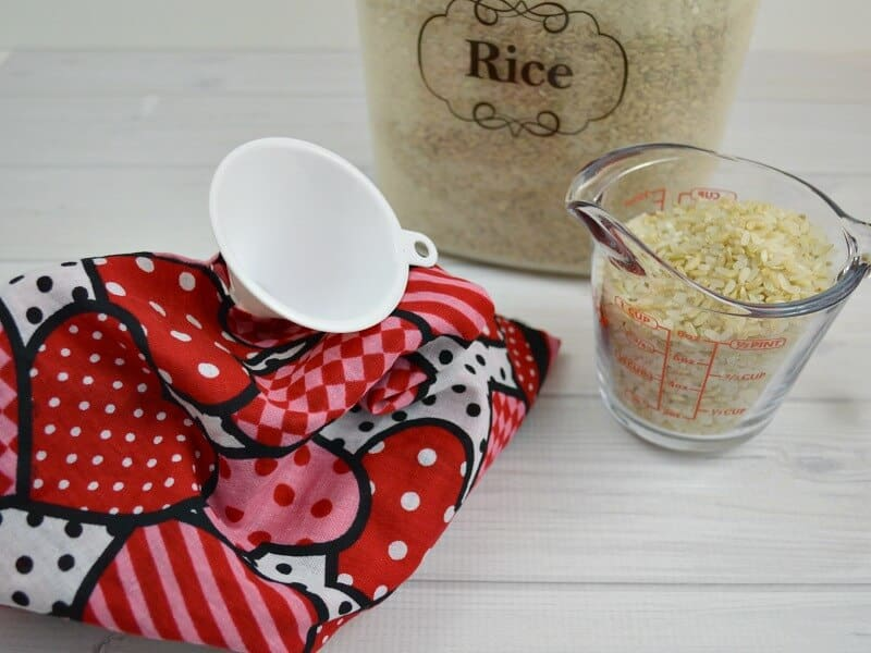 RIce in cup with funnel filling heating pad