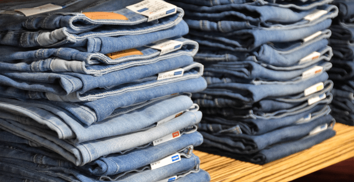 Two stacks of jeans on a wood shelf