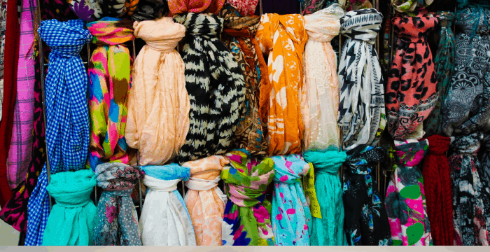 brightly colored scarves hanging on rod