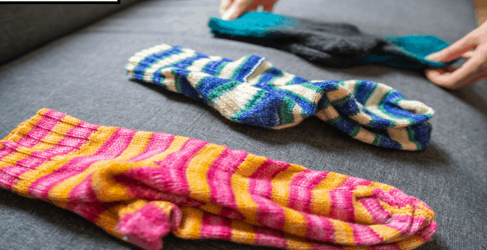 3 pairs of colorful socks laying on black table