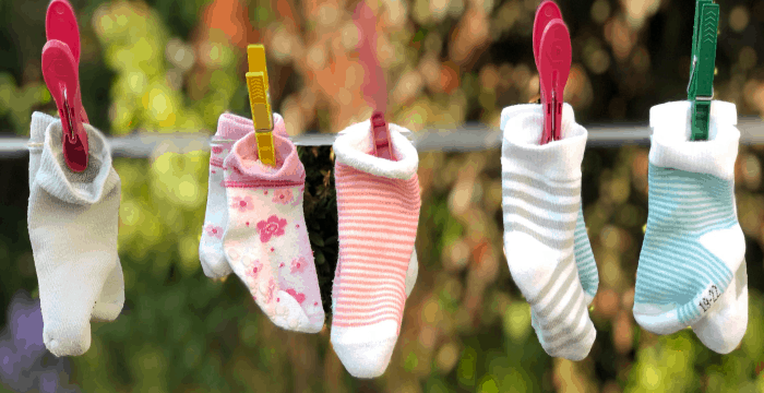 3 pairs of children's socks hung on clothes line with wood clothespins