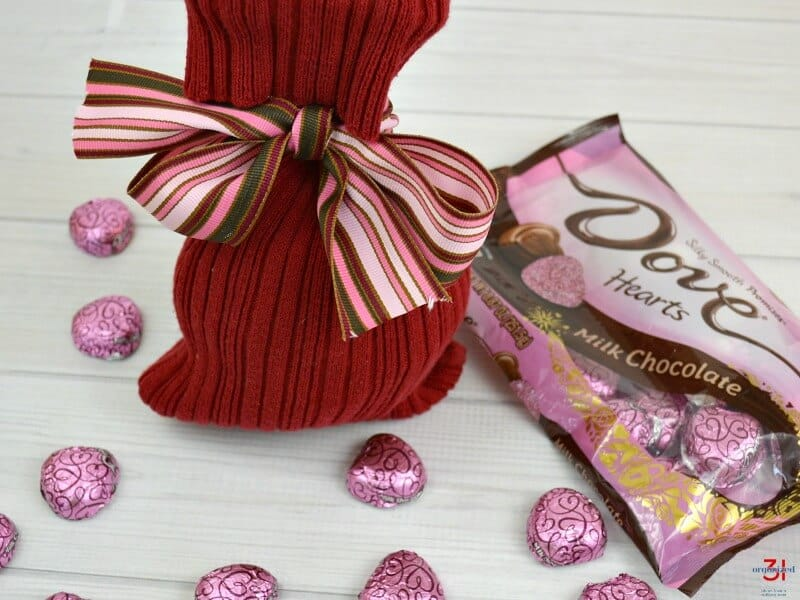 Red bag with pink and red bow, bag of chocolate heart candy and candies scattered