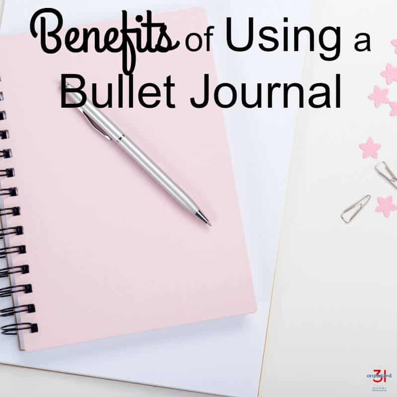 pink spiral notebook with silver pen on white table with title text reading Benefits of Using a Bullet Journal
