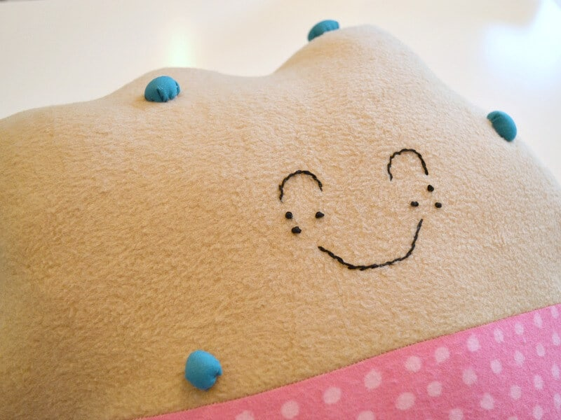 close up of embroidered smiling face on brown pillow with pink polka dot at bottom