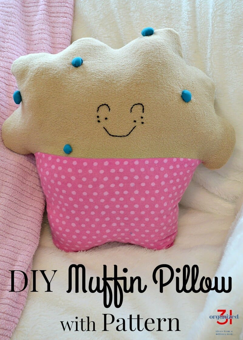 handmade pillow that looks like a muffin in a pink cupcake paper with smiling face with title text reading DIY Muffin Pillow with Pattern