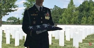 Soldier in dress uniform holding folded flag in cemetery.