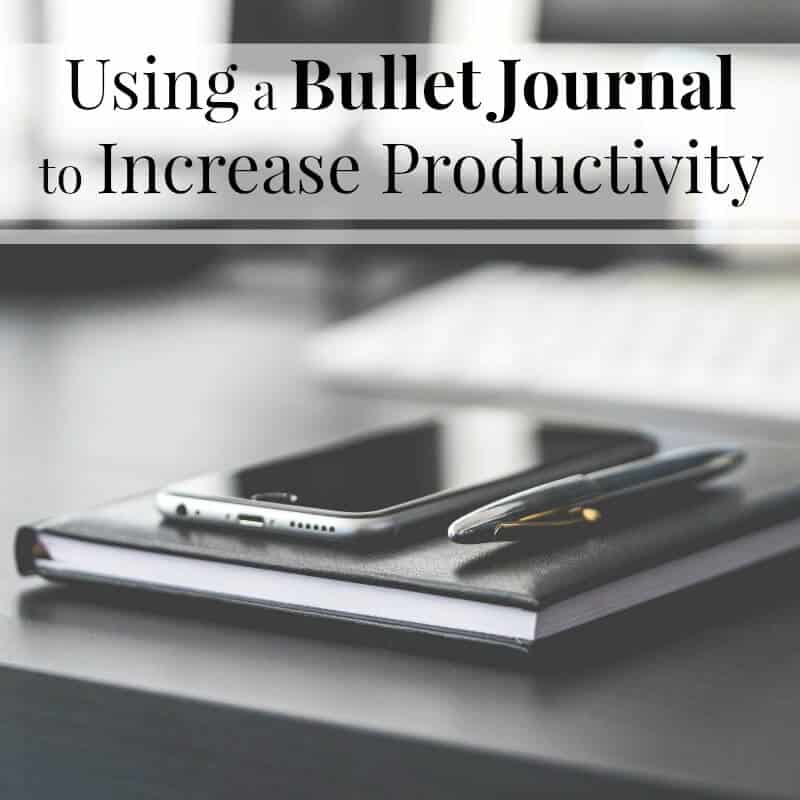 Ever wondered how to use a bullet journal to be more productive? Three key reasons that you'll be more focused, organized & productive. - Black cell phone and pen sitting on top of black journal on top of a black desk.