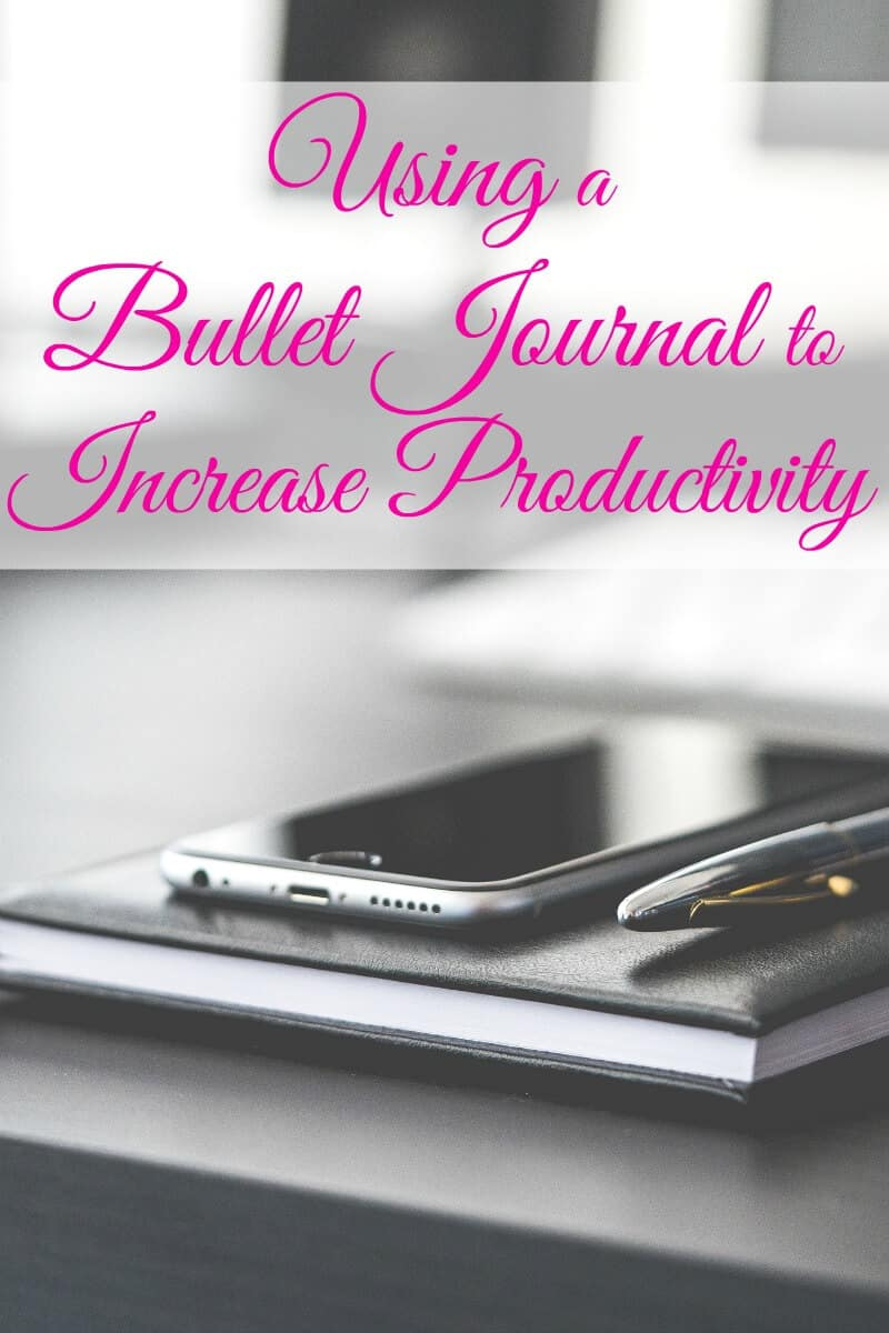 Black cell phone and pen sitting on top of black journal on top of a black desk with text overlay reading Using a Bullet Journal to Increase Productivity
