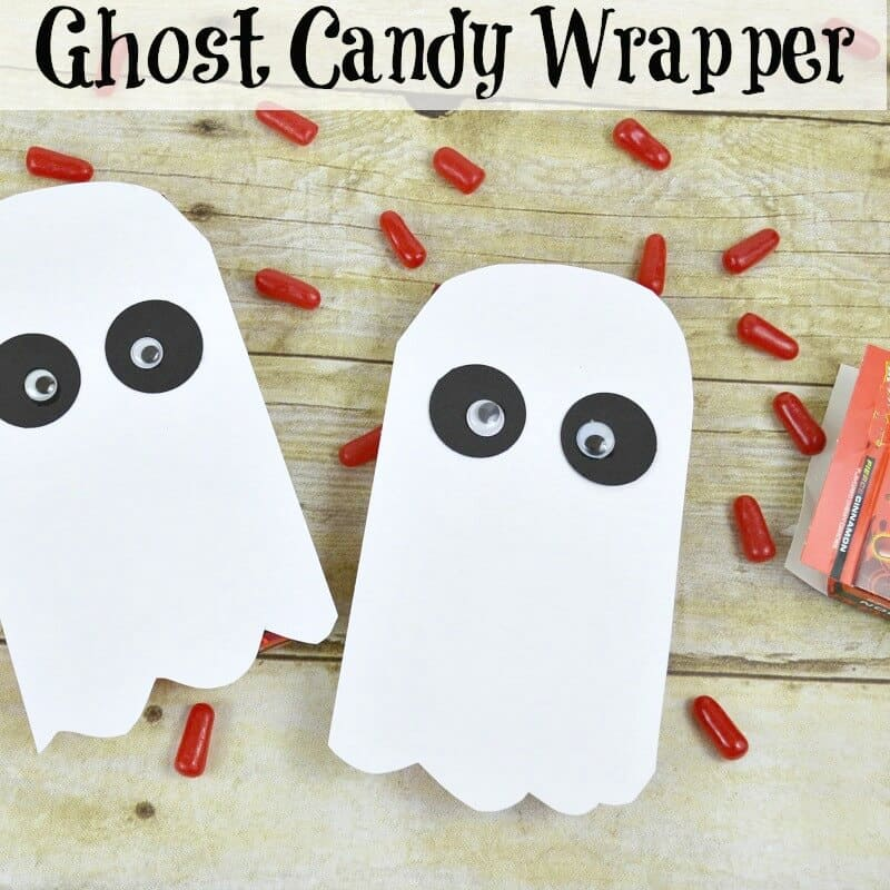 Two ghost crafts with candy scattered in background.
