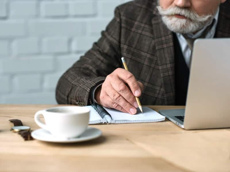 Older man with beard, writing in notebook, with laptop, coffee and watch nearby