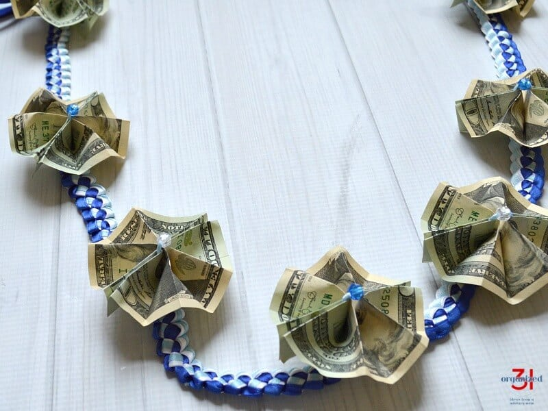 The Hawaiian tradition of giving a money for graduation is a festive and memorable gift. This money lei tutorial is easy to do and makes a more comfortable to wear graduation lei.