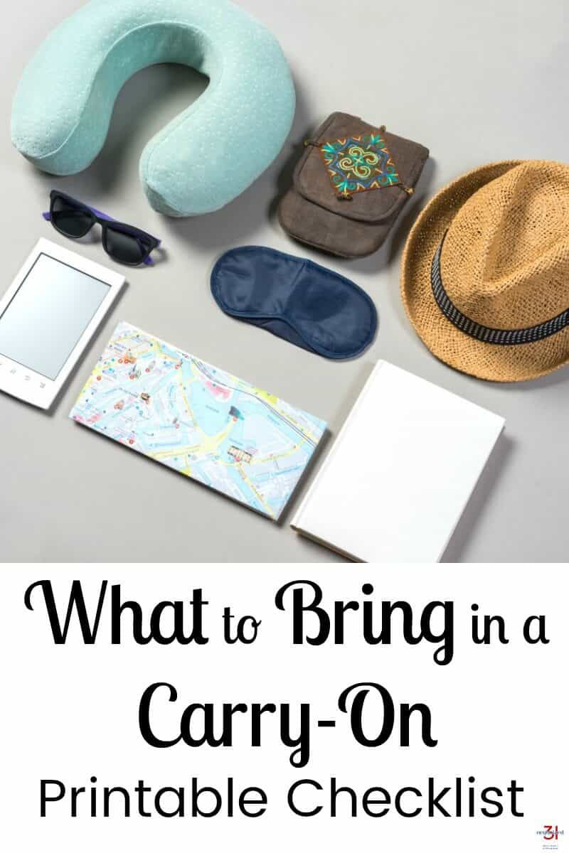 neck pillow, small bag, straw hat, sun glasses, sleep mask, reader, map and book neatly laid out on a table