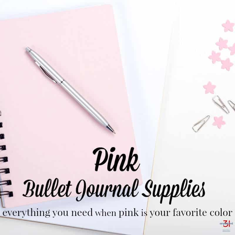 silver pen on pink notebook, with pink stars and paperclips next to it