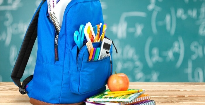 blue backpack filled with school supplies on desk with stack of notebooks and apple in front of green chalkboard
