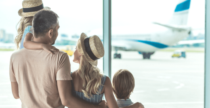 close up of Family standing with arms around each other in airport looking out window at plane