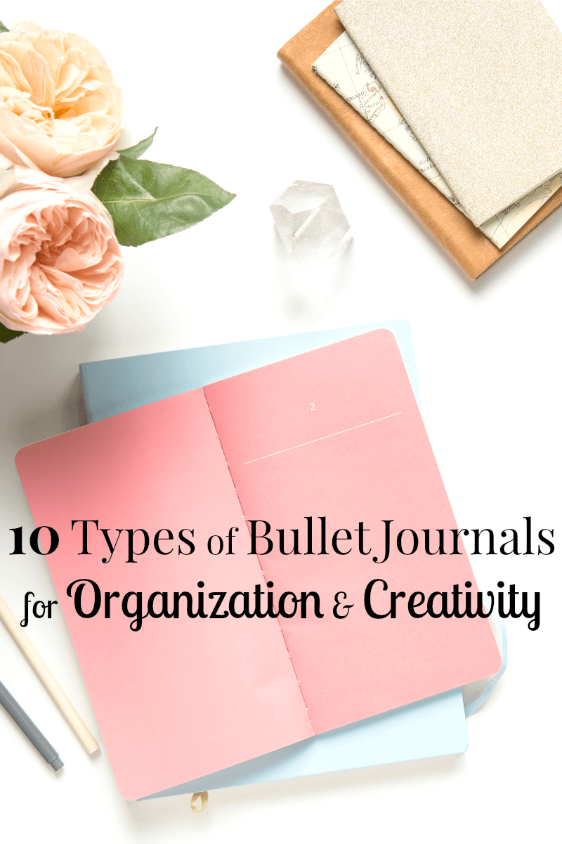 open pink journal on top of blue journal with stack of 3 journals and flowers nearby with title text overlay reading 10 Types of Bullet Journals for Organizing and Creativity