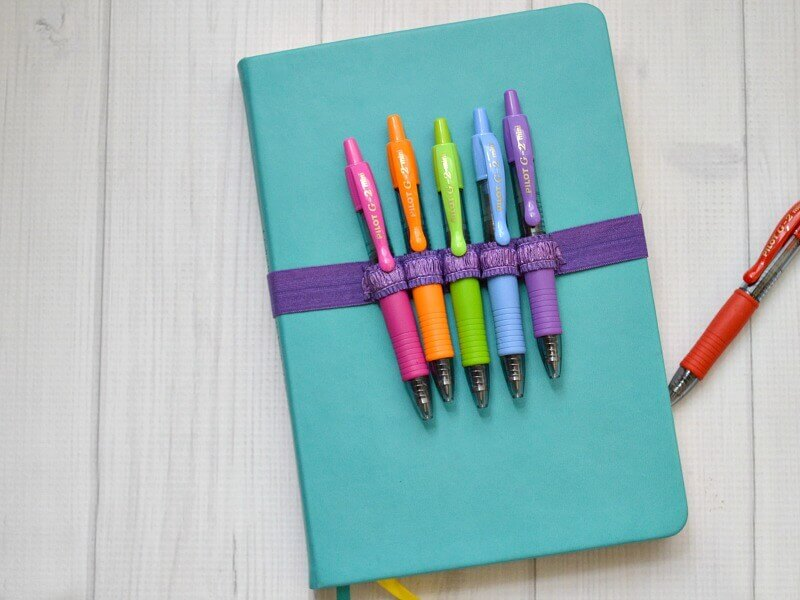5 colorful pens in purple strap on blue journal