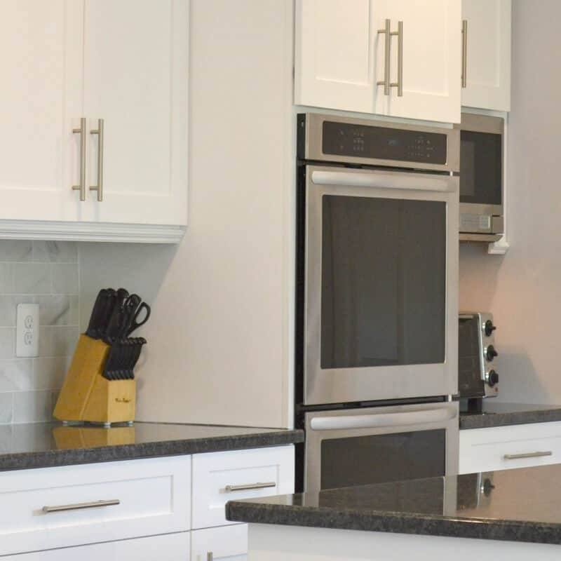 Stainless steel double oven in white kitchen with black counters