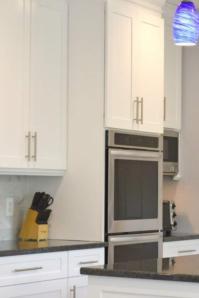Stainless steel double oven in white kitchen with black counters and blue pendant light
