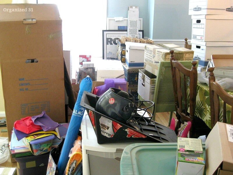piles of boxes and items in dining room