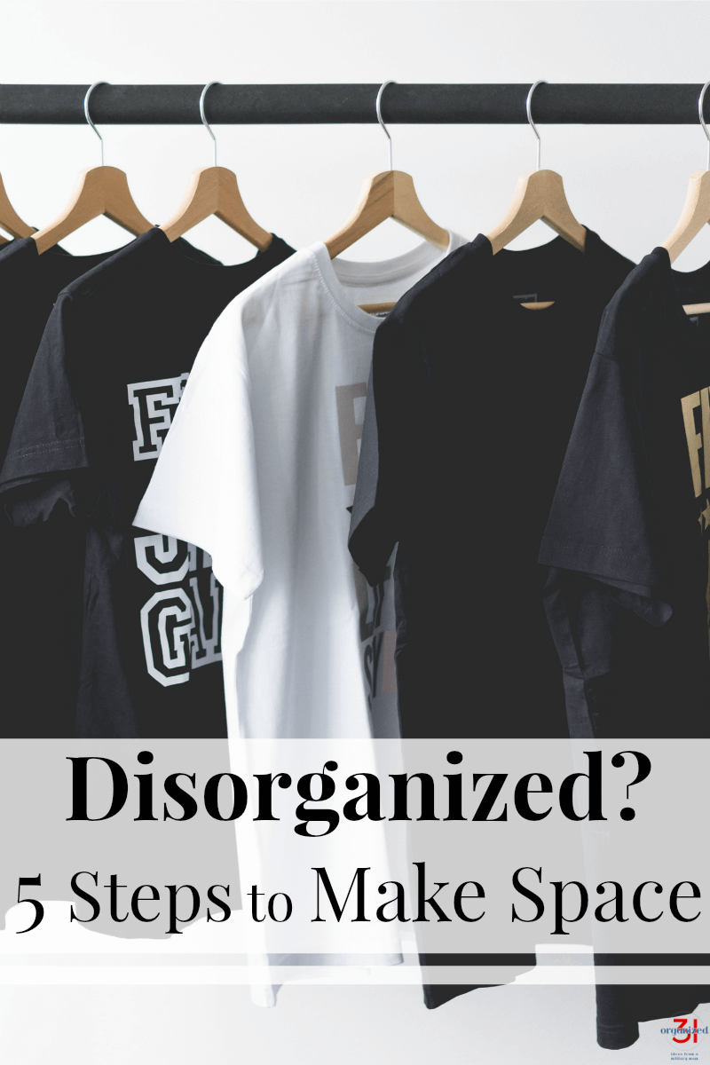 black and white tee-shirts hanging neatly on wood hangers on black rod
