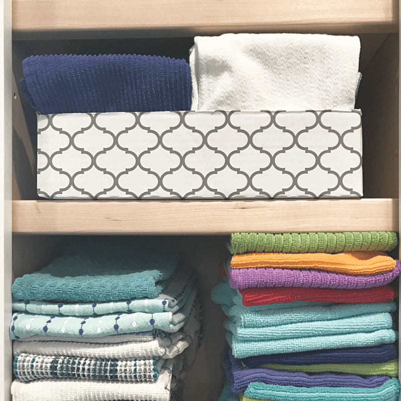 Two shelved in cabinet with stacked towels and colorful rags.