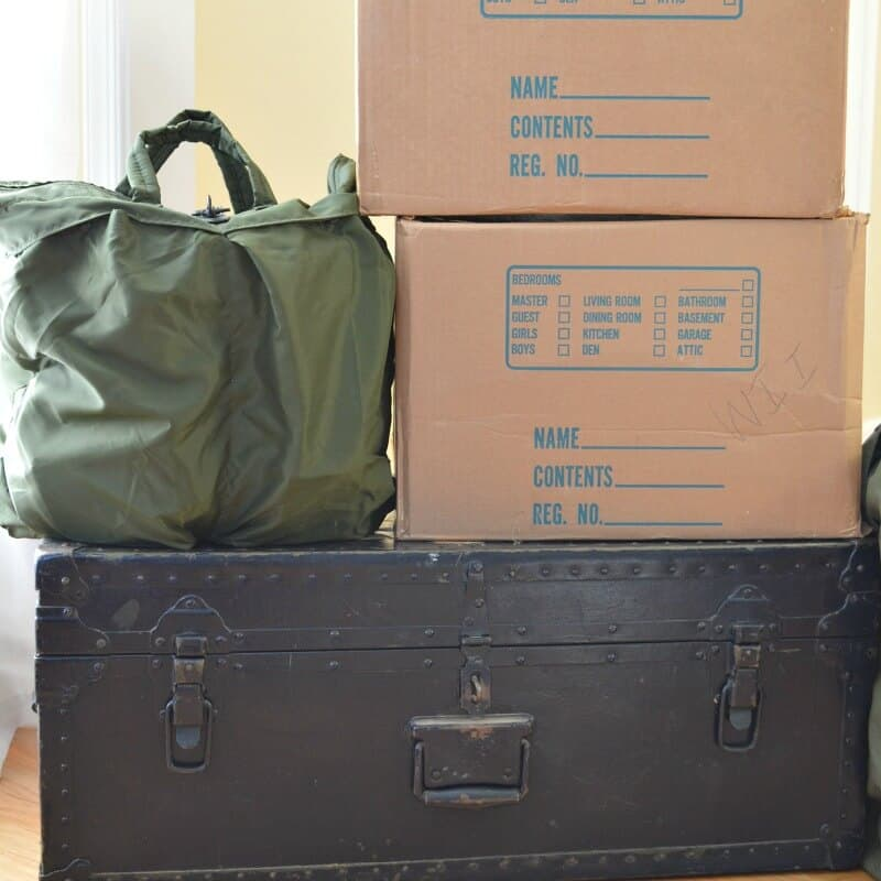 green footlocker with two moving boxes and green Army bag stacked on top