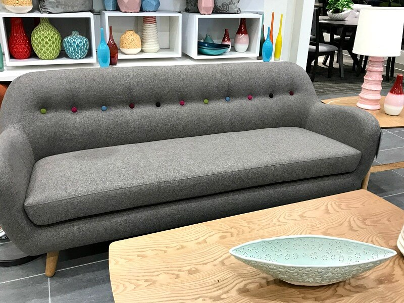 Grey couch with coffee table and colorful vases