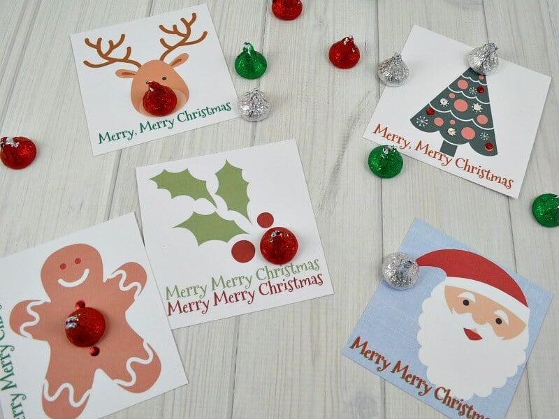 printed Christmas gift tags embellished with candy on white wood table