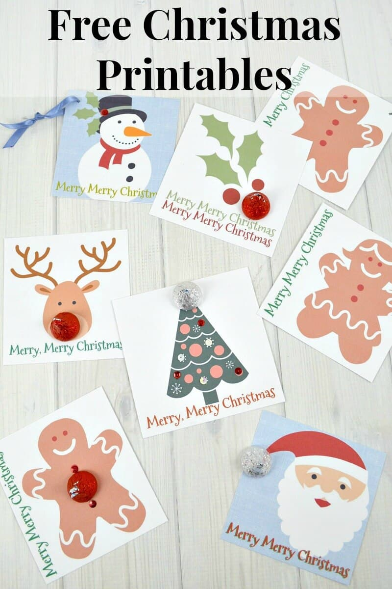 Numerous Christmas gift tags in different colors with different designs on white wood table with title text reading Free Christmas Printables
