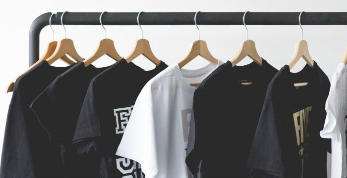 white and black tee-shirts on wood hangers on black clothes hanger