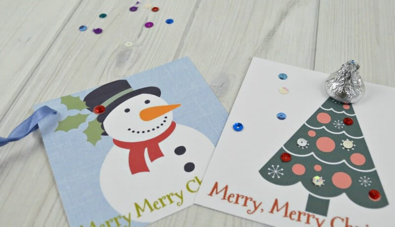 close up of 2 Christmas gift tags with sequins scattered on white table