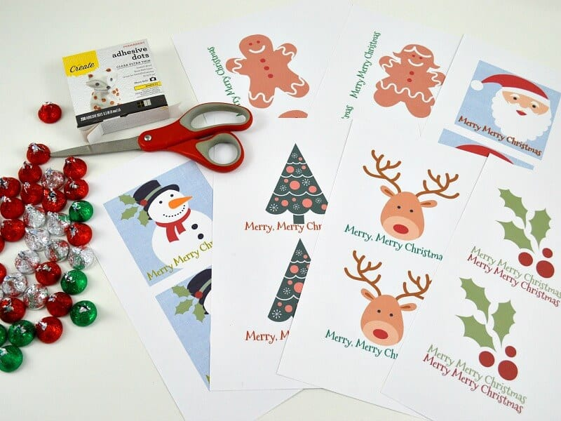 stack of paper with gift tags printed on them, red scissors, pile of candy and glue dots on white table