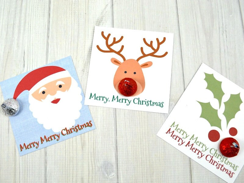 3 Christmas gift tags with added candy embellishment on white wood table