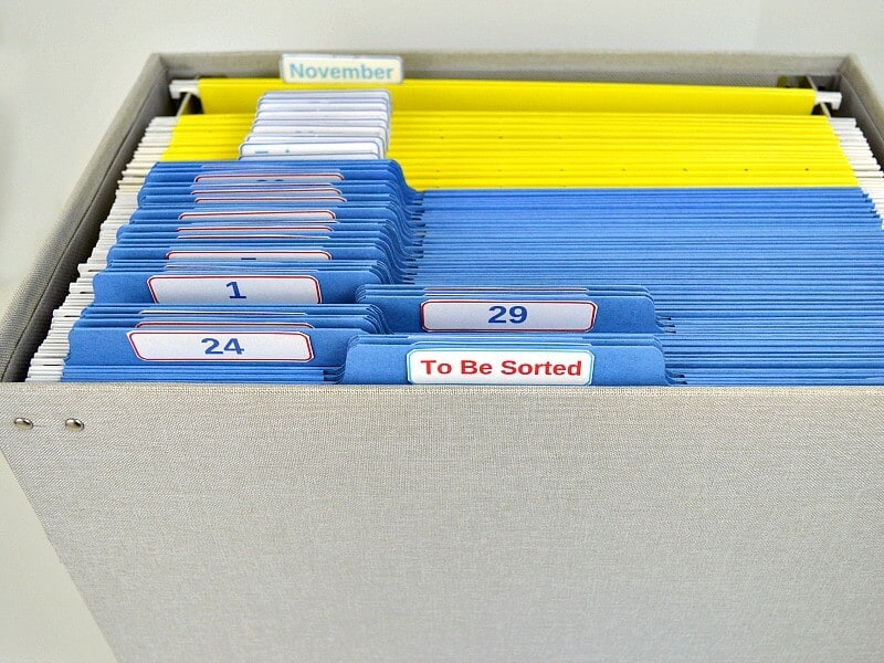 Staying on top of paperwork and life is much easier with this Organized 31 Tickler File for paper and task management. - grey file box with blue and yellow files