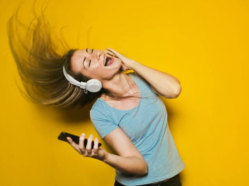 Woman listening to head phones - A complete gift guide for the tech lover - 10 gift ideas they'll love for family and friends of all ages.