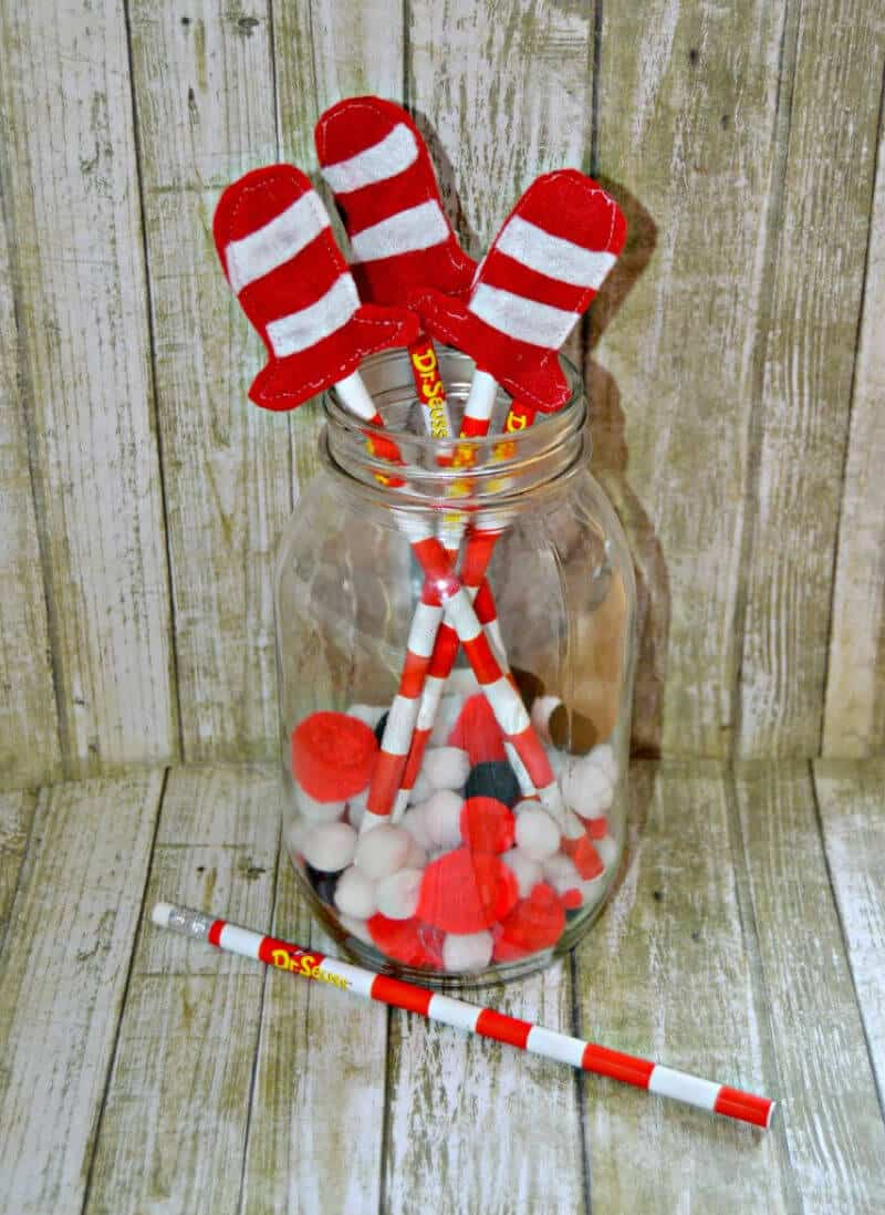 glass jar with Cat in the Hat pencil toppers on red and white striped pencils
