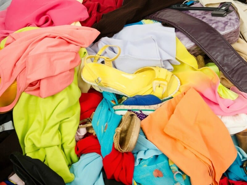 messy pile of brightly colored clothes and shoes