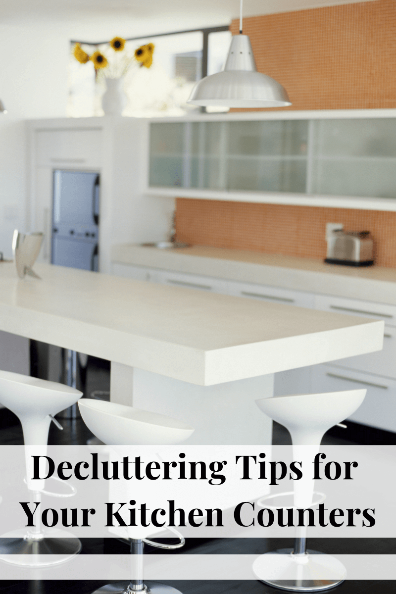 a kitchen counter and the rest of the kitchen in the background with title text reading Decluttering Tips for Your Kitchen Counters