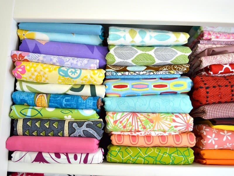 It's simple to fold fabric to keep it neat and tidy in your sewing or craft room. Folding fabric in uniform sizes makes it easier to keep it organized. - Close up of stacks of neatly folded fabric on shelf.