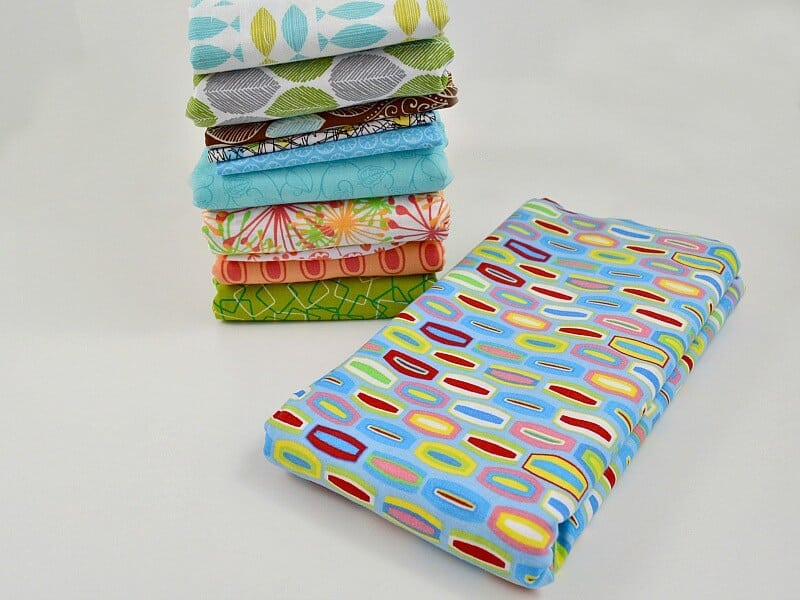 It's simple to fold fabric to keep it neat and tidy in your sewing or craft room. Folding fabric in uniform sizes makes it easier to keep it organized. - Neatly folded stack of fabrics with one piece of fabric in foreground.