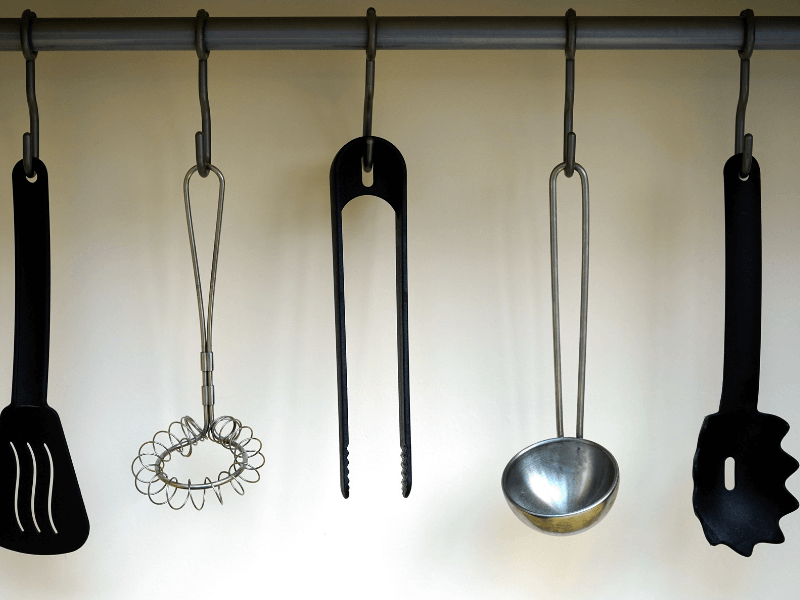 These tried and true organization tips for the kitchen will help you organize your kitchen and make it work for your unique situation and needs. - Image of kitchen ladles on hooks.