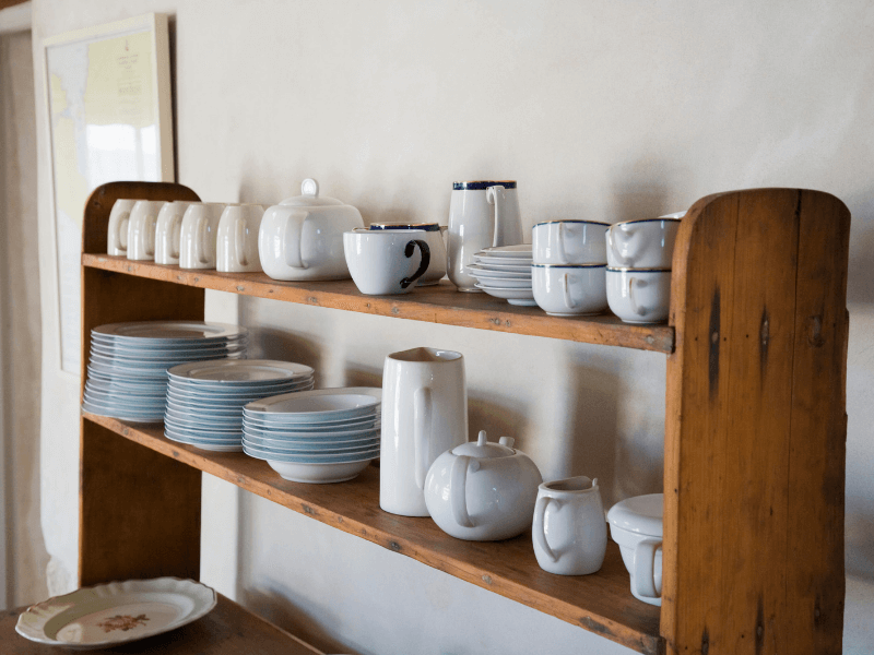 These tried and true organization tips for the kitchen will help you organize your kitchen and make it work for your unique situation and needs. - Image of dishes on kitchen shelf.