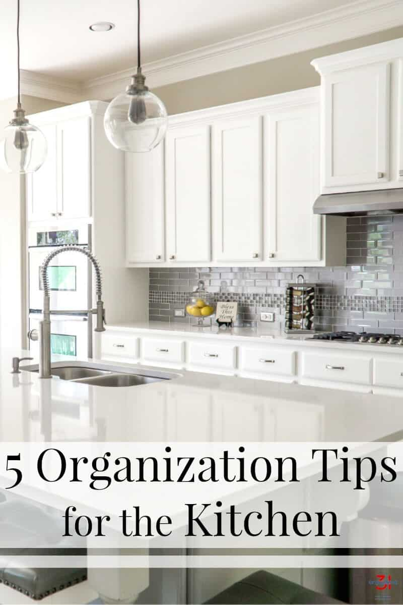 These tried and true organization tips for the kitchen will help you organize your kitchen and make it work for your unique situation and needs. - Image of tidy kitchen with white cabinets.