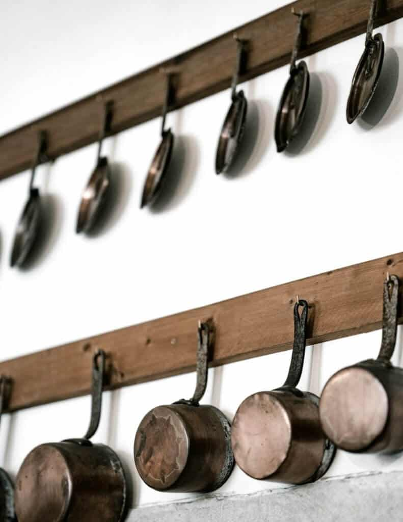Copper pots hanging from hooks on wall