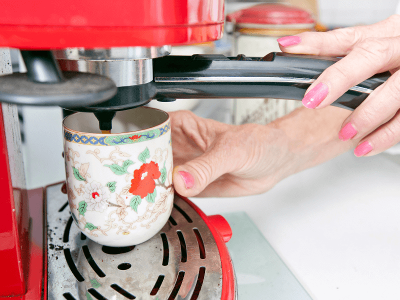 a woman's hands filling up a coffee cup under a coffee maker